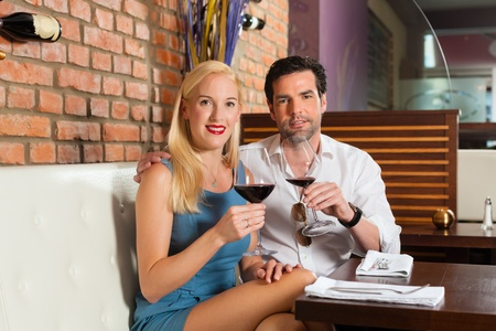 Attractive young couple drinking red wine in restaurant or bar, it might be the first date Stock Photo - 13503357