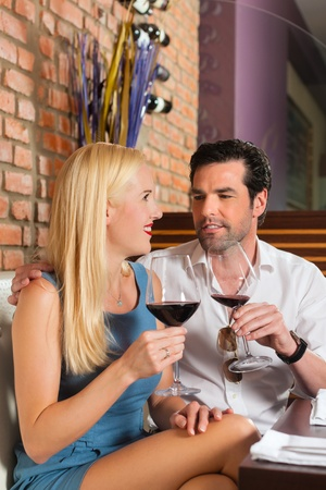 Attractive young couple drinking red wine in restaurant or bar, it might be the first date Stock Photo - 13503289