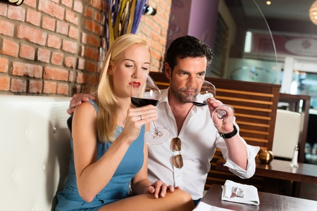 Attractive young couple drinking red wine in restaurant or bar, it might be the first date Stock Photo - 13503392