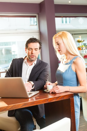 Working colleagues - a man and a woman - sitting in cafe working and drinking coffee photo