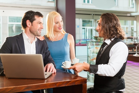 shop assistant: Working colleagues - a man and a woman - sitting in cafe working, the waiter serves coffee