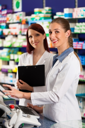 cashpoint: Pharmacist with female assistant in pharmacy standing at the cashpoint