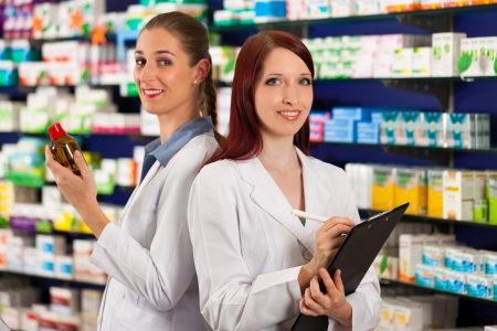 stocktaking: Pharmacist with female assistant in pharmacy standing in front of shelf with drugs Stock Photo