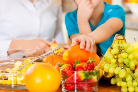 child food: Healthy eating - mother and child sitting in the kitchen with different kinds of fruits for breakfast food Stock Photo