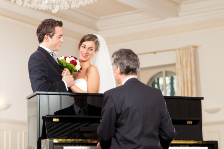wedding veil: Bridal couple in front of a piano, the pianist is playing a waltz