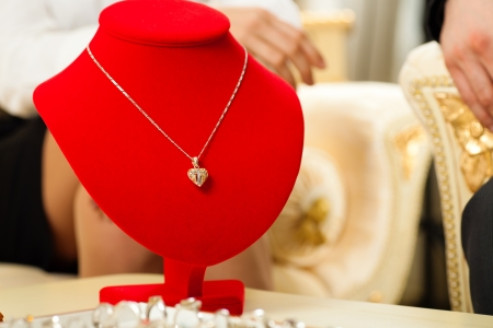jeweller: Man giving his wife a necklace as a gift, the necklace is still hanging on the bust Stock Photo