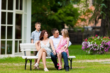 Young happy family sitting in the sun in front of their new home on a bench - it is a villa photo