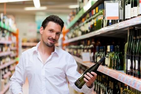 Portrait of smiling young man holding liquor bottle at supermarket photo