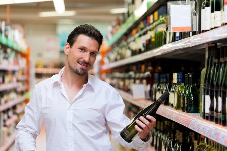 Portrait of smiling young man holding liquor bottle at supermarket Stock Photo - 13709142
