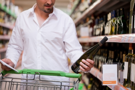 Young male shopper looking at liquor bottle at supermarket Stock Photo - 13712578