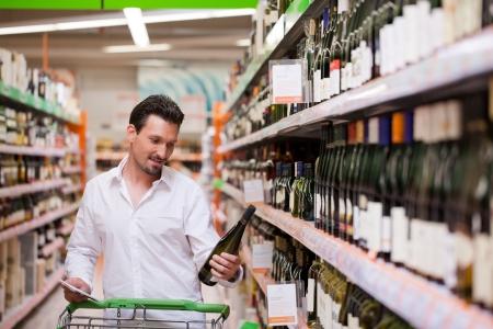 botella de licor: Joven mirando la botella de vino en el supermercado