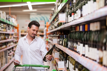 wine store: Young man looking at bottle of wine in supermarket Stock Photo
