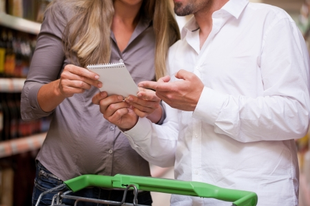 Young couple conversing while shopping together at supermarket photo