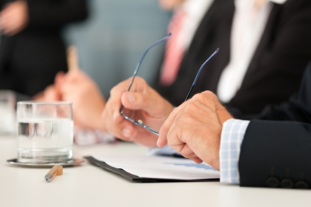 lawyer: Business - people sitting in a meeting, close-up on hands and man in the front