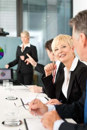 Business - presentation within a team, a female, colleague is standing on the flipchart photo