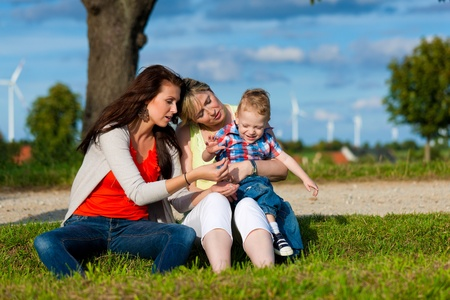 Family - Grandmother, mother and child sitting and playing in garden Stock Photo - 13709243