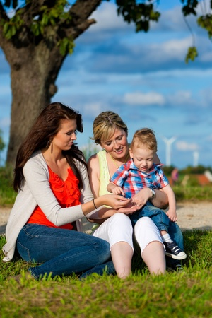 Family - Grandmother, mother and child sitting and playing in garden Stock Photo - 13709186