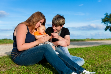 Family - mother, father and child sitting and playing in garden photo