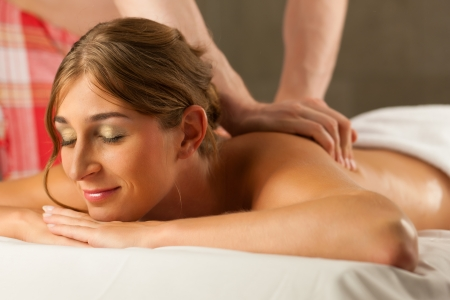 Woman enjoying a wellness back massage in a spa, she is very relaxed  close-up ; the masseur could be her boyfriend   photo