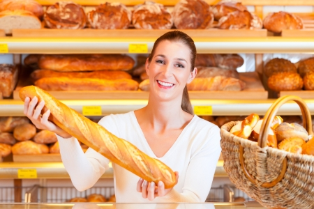 Vrouw bakker of verkoopster in haar bakkerij met vers gebak en bakkerijproducten, een stokbrood