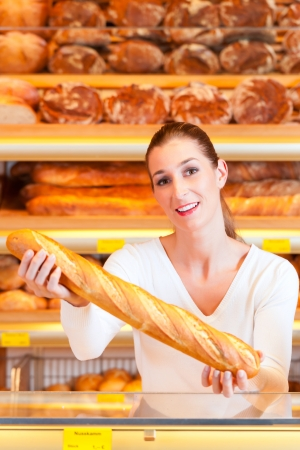 Female baker or saleswoman in her bakery with fresh pastries and bakery products, a baguette photo