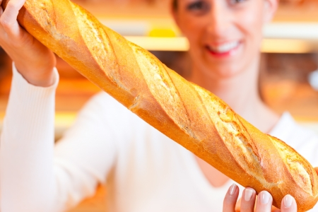 bakery store: Female baker or saleswoman in her bakery with fresh pastries and bakery products, a baguette