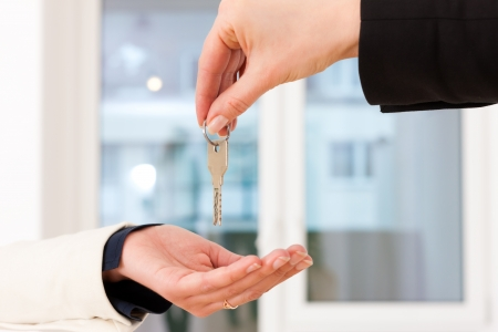 Young realtor is giving the keys to an apartment to the tenant, close-up on keys and hands photo