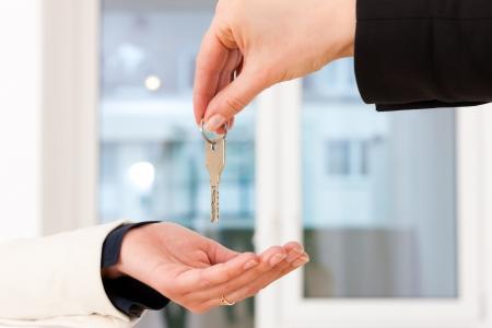 Giovane agente immobiliare sta dando le chiavi di un appartamento al locatario, close-up sui tasti e le mani
