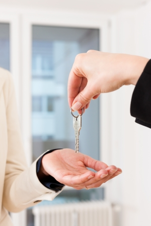 Young realtor is giving the keys to an apartment to the tenant, close-up on keys and hands Stock Photo - 13712555