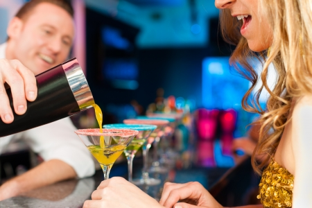 barman: Young people in club or bar drinking cocktails and having fun; the barkeeper is mixing drinks