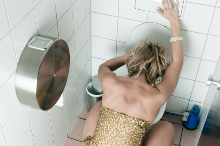 Woman had too many drinks and is drunk and is throwing up in the toilet photo