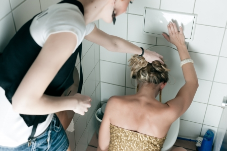 Woman had too many drinks and is drunk and is throwing up in the toilet, a friend is helping her photo