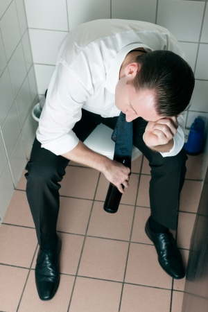 toilette: Young man is sitting drunk on a toilette, presumably he is in a club
