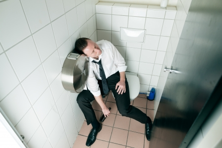 unconscious: Young man is sitting drunk on a toilette, presumably he is in a club
