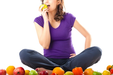 Healthy eating, happy woman with fruits and vegetables is eating a pear  photo