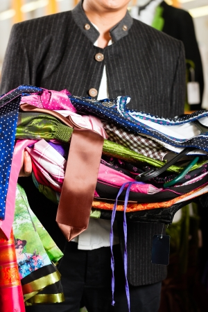 clothing rack: Traditional clothes - young man is buying Tracht or dirndl in a shop, he has lots of dirndl in his arms, cropped image
