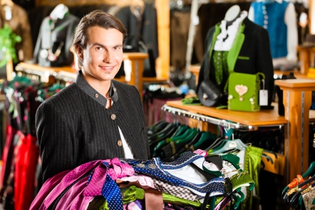 selling off: Traditional clothes - young man is buying Tracht or dirndl in a shop, he has lots of dirndl in his arms Stock Photo