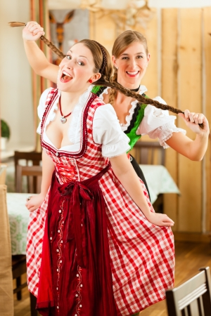 dirndl: Two young women in traditional Bavarian Tracht in restaurant or pub drawing on hair