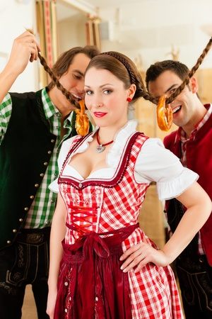 joking: Young people in traditional Bavarian Tracht in restaurant or pub having fun and making jokes