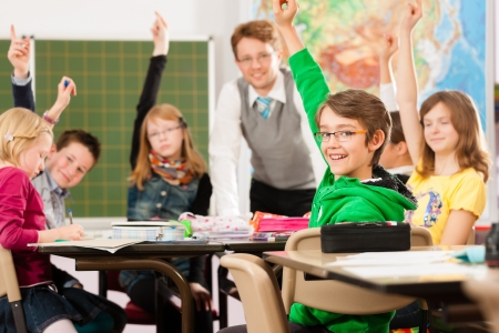 elementary kids: Education - Pupils and teacher learning at elementary or primary school in the classroom Stock Photo