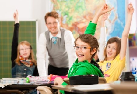 Education - Pupils and teacher learning at elementary or primary school in the classroom Stock Photo - 13708817