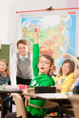 Education - Pupils and teacher learning at elementary or primary school in the classroom Stock Photo - 13708928