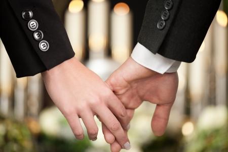luto: La religión, la muerte y el dolor - pareja en el funeral consolando a tomarse de las manos unos a otros en vista de la pérdida Foto de archivo