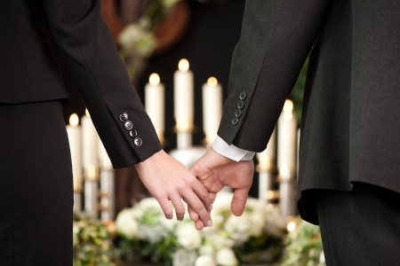 La religión, la muerte y el dolor - pareja en el funeral consolando a tomarse de las manos unos a otros en vista de la pérdida Foto de archivo