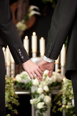 funeral parlor: Religion, death and dolor  - couple at funeral holding hands consoling each other in view of the loss