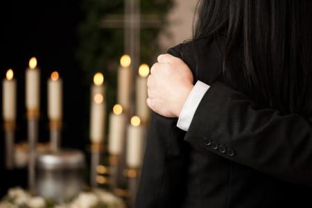 захоронение: Религия, смерть и боль - Пара на похоронах утешая друг друга в связи с потерей