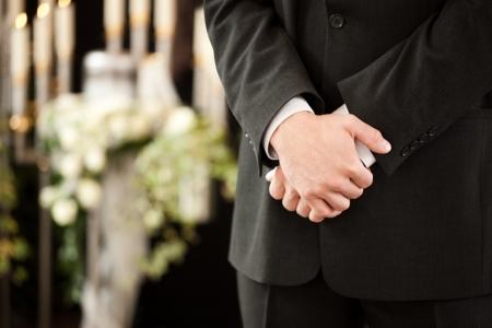 luto: La religión, la muerte y el dolor - empresario de pompas fúnebres en el funeral de pie en frente o de la urna