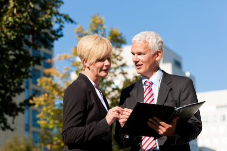 experienced: Business people - mature or senior - talking outdoors and discussing a document