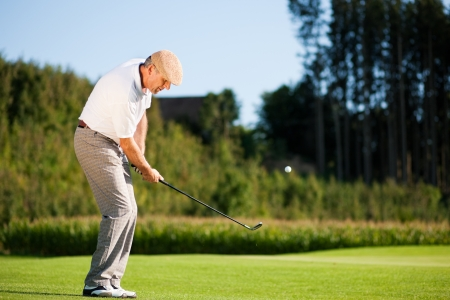 Senior golfer doing a golf stroke, he is playing on a wonderful summer afternoon Stock Photo - 14125541