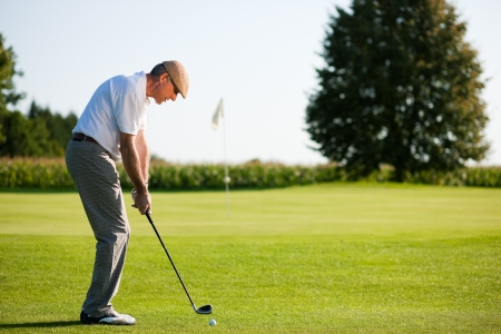 he: Senior golfer doing a golf stroke, he is playing on a wonderful summer afternoon